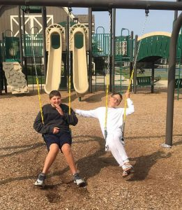 Henry and JR on swings at a playground