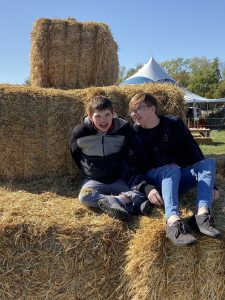Brothers, Evin and Mathew Perry sitting on hay bales