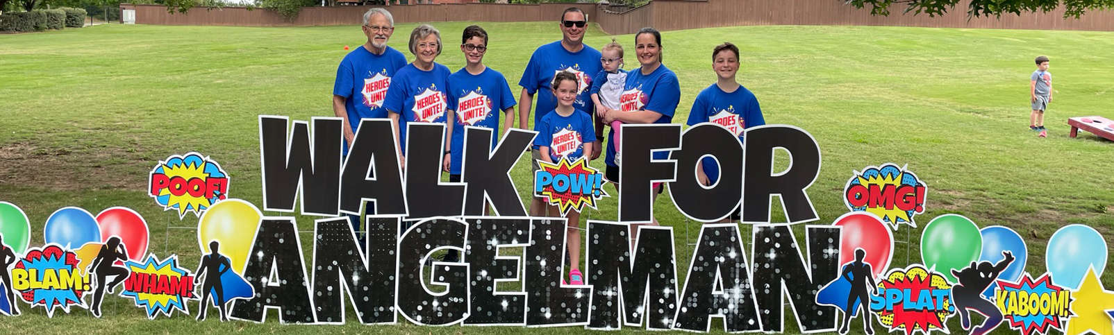 Family standing behind a Walk for Angelman sign